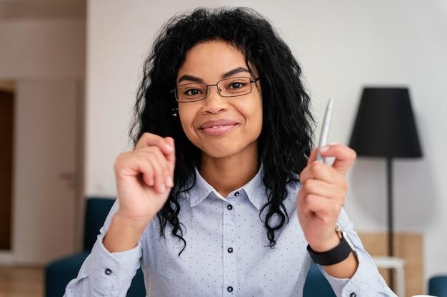 Vue de face de l'adolescente smiley à la maison pendant l'école en ligne