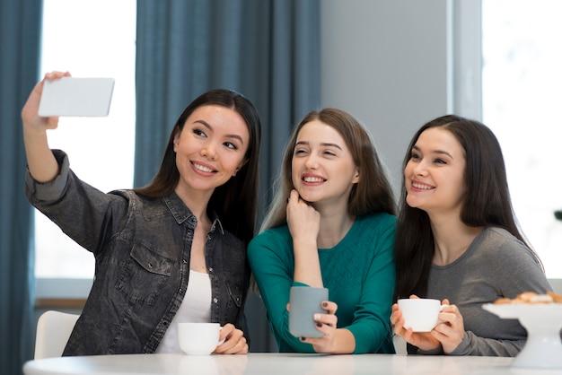 Vue de face adorables jeunes femmes prenant un selfie ensemble