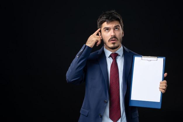 Vue de face d'un adulte ahuri en costume tenant un espace libre pour écrire et pointer quelque chose sur le côté droit sur un mur sombre isolé