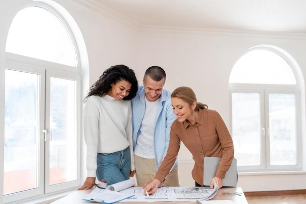 Vue de face de l'agent immobilier féminin montrant un nouveau plan de maison pour couple