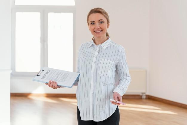 Vue de face de l'agent immobilier féminin smiley dans la maison vide tenant le presse-papiers