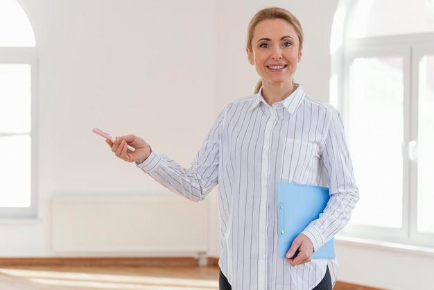 Vue de face de l'agent immobilier féminin smiley avec presse-papiers dans la maison vide