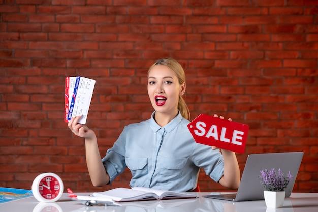 Vue de face de l'agent de voyage détenant des billets et de la plaque signalétique de vente assistant directeur mondial carte de l'occupation professionnel de l'emploi de l'agence