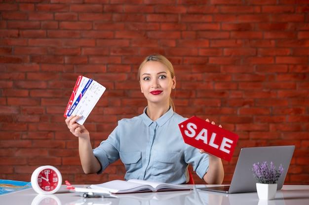 Vue de face de l'agent de voyage détenant des billets et de la plaque signalétique de vente assistante de l'agence mondiale de l'occupation gestionnaire de travail professionnel