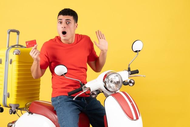 Vue de face agité jeune homme sur cyclomoteur tenant une carte de crédit