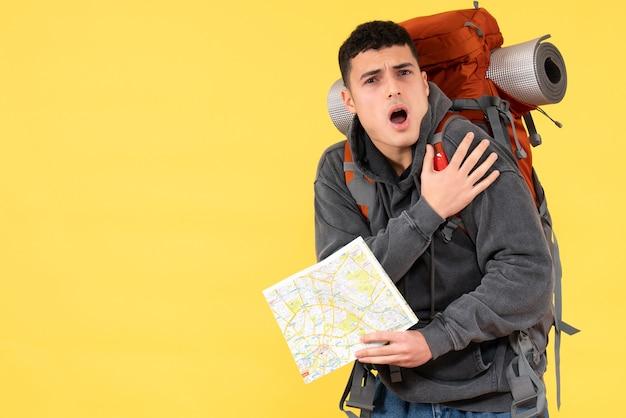 Vue de face agité jeune homme avec sac à dos rouge tenant la carte de voyage