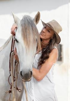 Vue de face d'une agricultrice plus âgée avec son cheval au ranch
