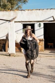 Vue de face de l'agricultrice portant une selle de cheval