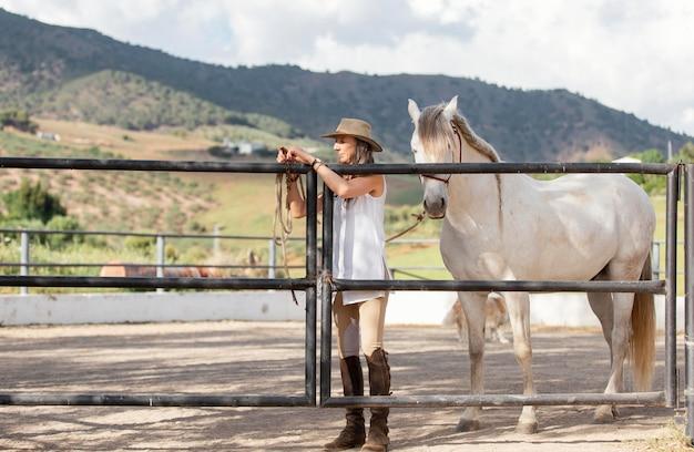 Vue de face de l'agricultrice avec son cheval au ranch