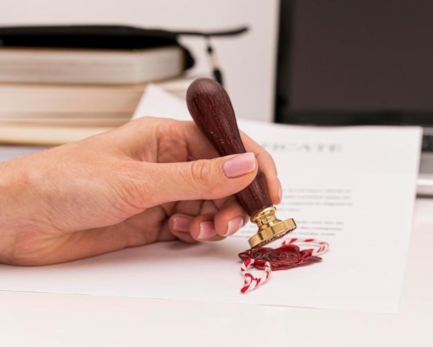Vue de face à l'aide d'un sceau de cire pour le certificat de diplôme