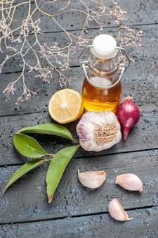 Vue de face de l'ail et de l'huile sur un bureau sombre aux couleurs mûres des légumes