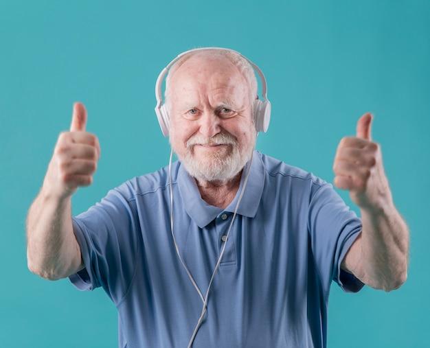 Vue de face aîné avec des écouteurs montrant signe ok