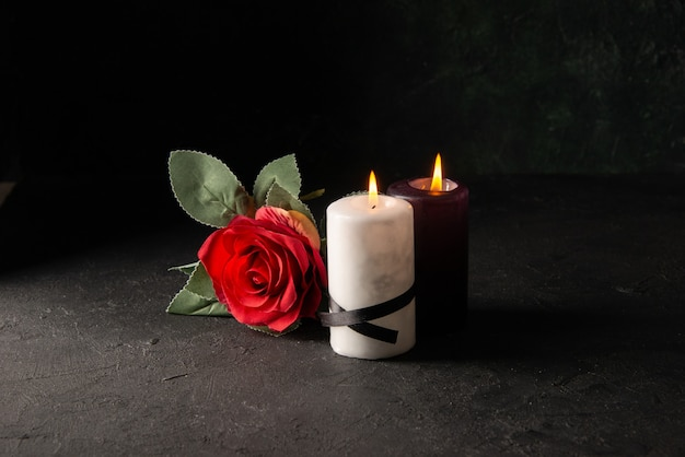 Vue de face d'allumer des bougies avec une fleur rouge sur fond noir