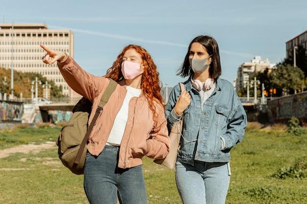 Vue de face des amies avec des masques à l'extérieur ensemble