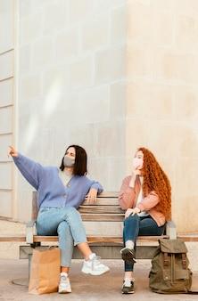 Vue de face des amies avec des masques faciaux à l'extérieur assis sur un banc avec copie espace
