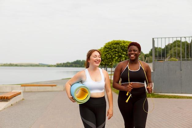 Vue de face d'amies smiley à l'extérieur essayant de faire de l'exercice