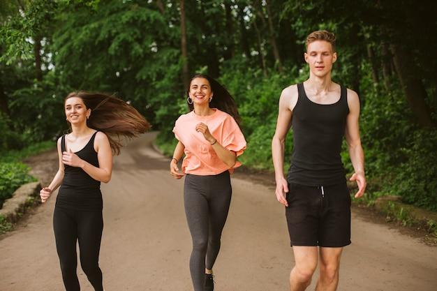 Vue de face amis courir dans la nature