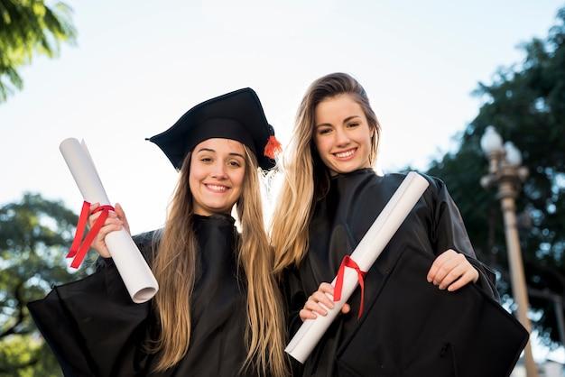 Vue de face des amis diplômés en regardant la caméra