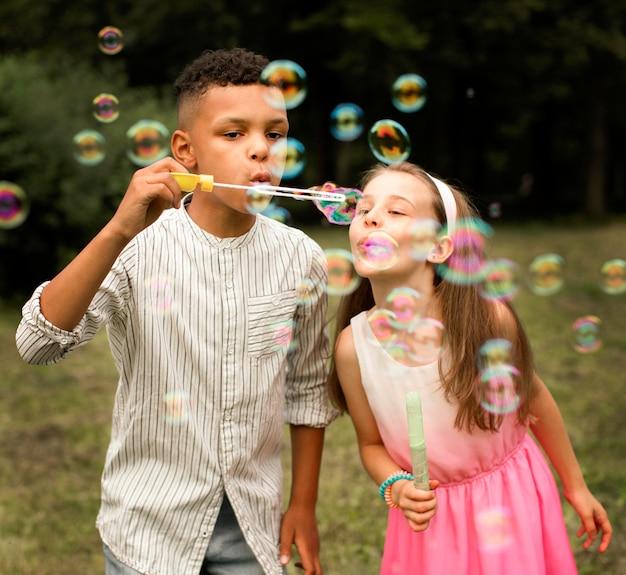 Vue de face d'amis faisant des bulles de savon
