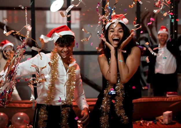 Vue de face des amis heureux célébrant le réveillon du nouvel an