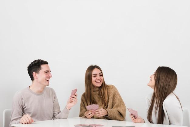 Vue de face des amis heureux en jouant aux cartes