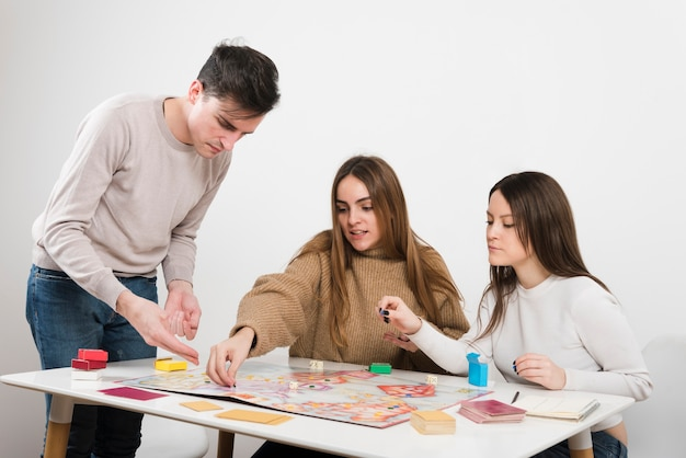 Vue de face des amis jouant à un jeu de société