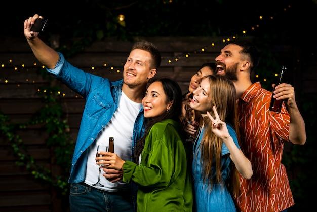 Vue de face des amis prenant un selfie