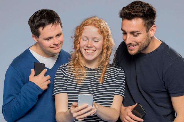 Vue de face amis regardant ensemble sur un téléphone
