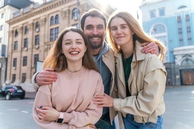 Vue de face d'amis smiley à l'extérieur dans la ville posant ensemble