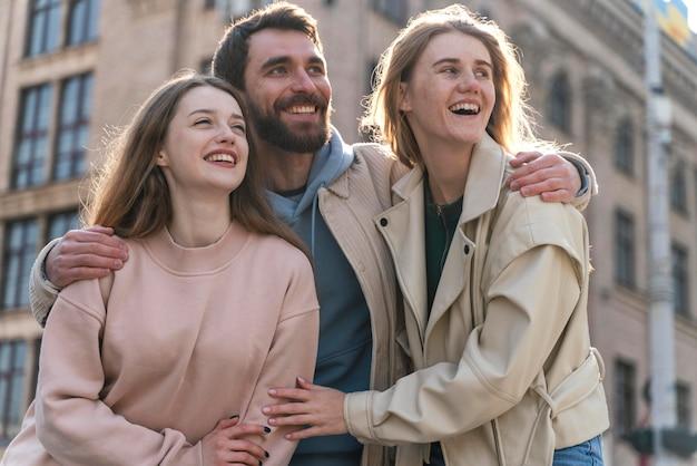 Vue de face d'amis smiley à l'extérieur dans la ville s'amuser ensemble