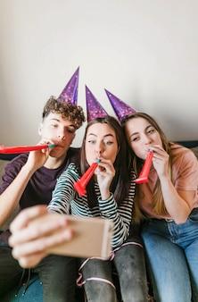 Vue de face des amis soufflant des cornes et prenant un selfie