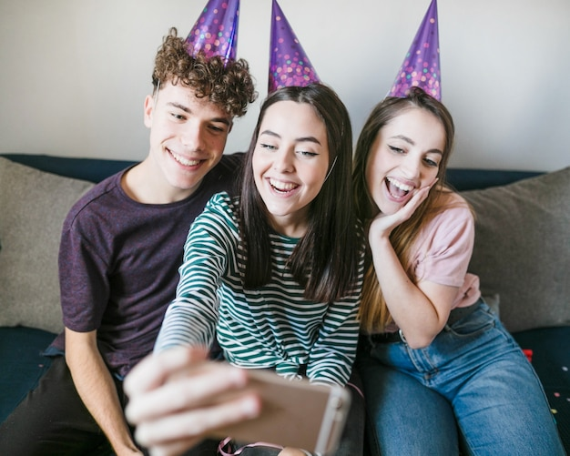 Vue de face d'amis souriants posant pour un selfie