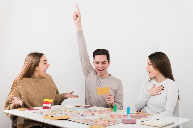 Vue de face des amis surpris en train de jouer à un jeu de société