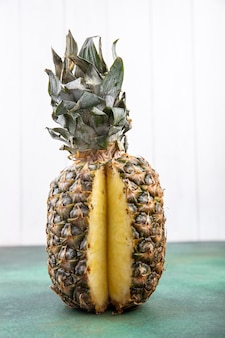 Vue de face de l'ananas avec une pièce découpée dans des fruits entiers sur une surface verte et une surface blanche