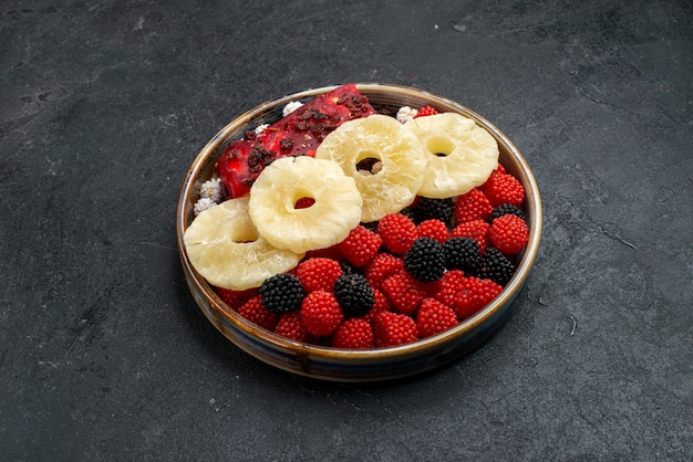 Vue de face anneaux d'ananas séchés avec des baies de confiture sur la surface gris foncé fruits raisins secs bonbons de sucre sucré photo