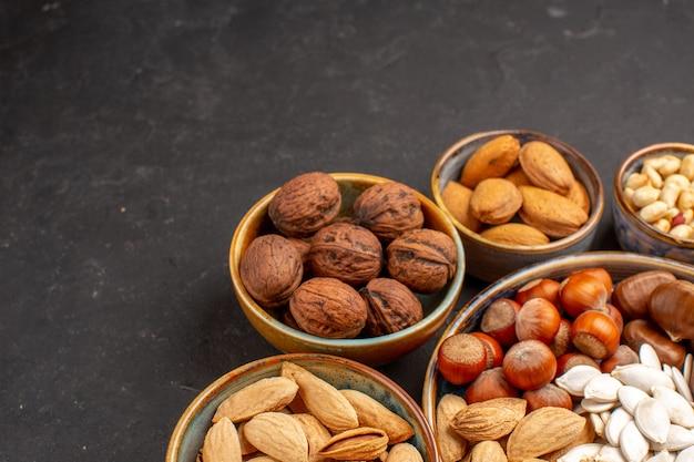 Vue de face des arachides de composition de noix et autres noix sur une surface sombre