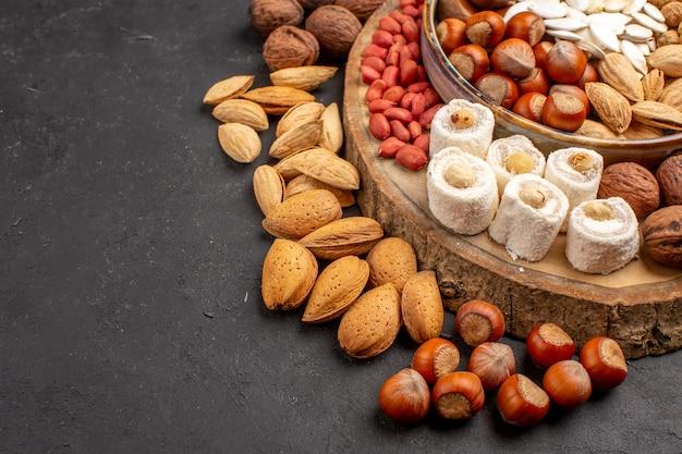 Vue de face des arachides de noix fraîches et autres noix sur une surface sombre