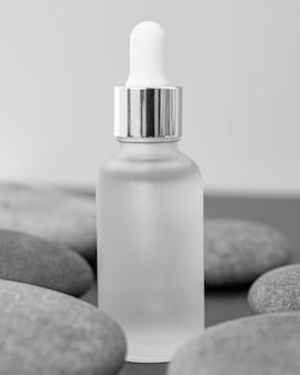 Vue de face de l'arrangement de compte-gouttes d'huile de peau avec des pierres
