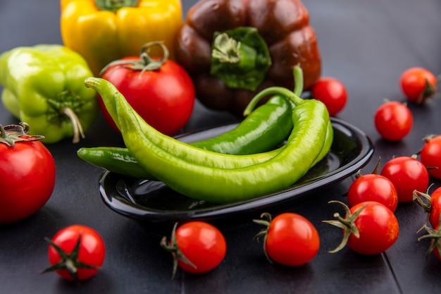 Vue de face de l'assiette de poivron avec tomates et autres poivrons autour de la surface noire