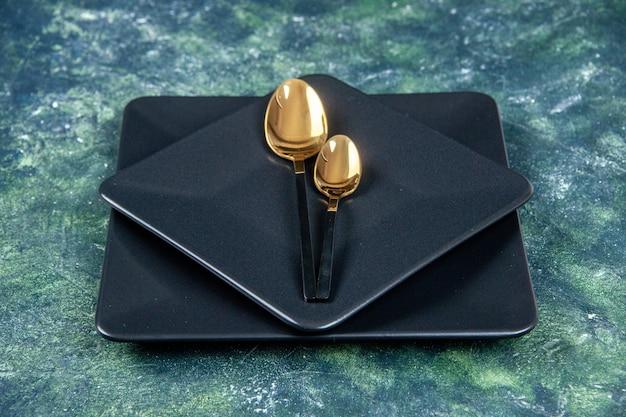 Vue de face assiettes noires avec cuillères dorées sur fond sombre