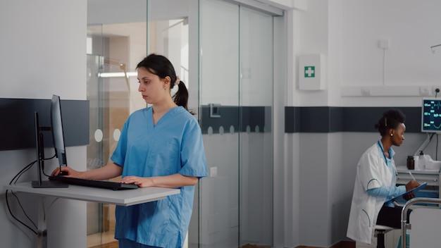 Vue de face de l'assistant tapant l'expertise médicale sur ordinateur