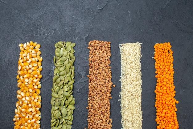 Vue de face d'un assortiment de grains de sarrasin graines de citrouille lentilles rouges grains de riz sur fond noir avec espace libre