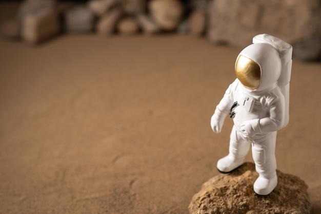 Vue de face de l'astronaute blanc autour des pierres sur le noir