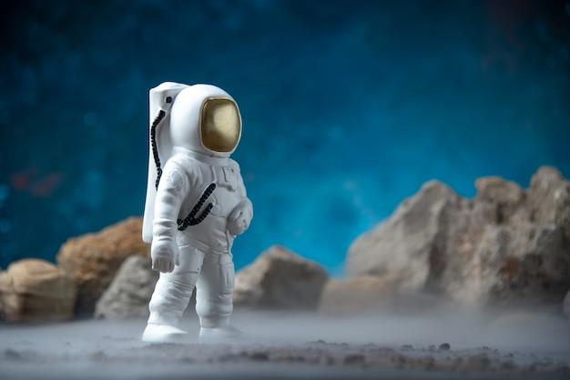 Vue de face d'un astronaute blanc avec des rochers sur une lune bleue fantastique de science-fiction cosmique
