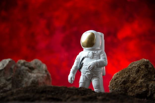 Vue de face de l'astronaute blanc avec des rochers sur la lune rouge fantastique de science-fiction cosmique