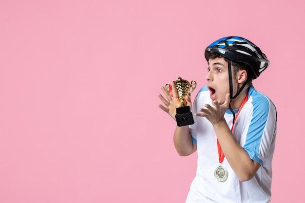 Vue de face de l'athlète masculin surpris tenant la coupe d'or avec casque