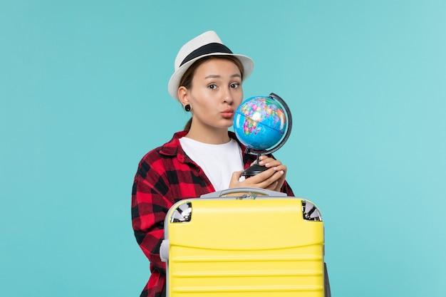 Vue de face attrayante femme tenant le globe et préparation pour le voyage sur l'espace bleu