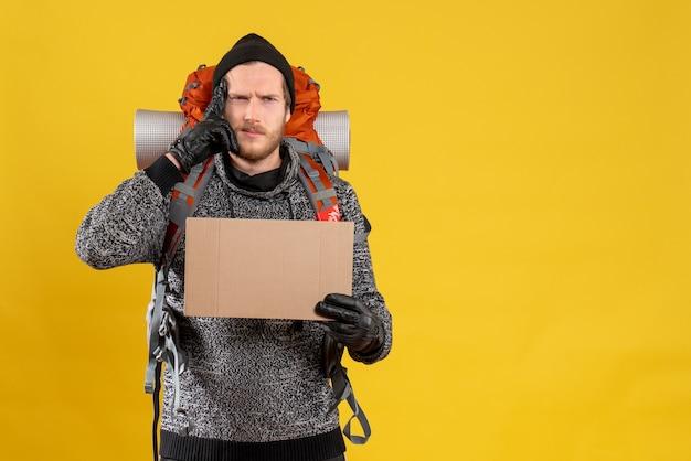Vue de face de l'auto-stoppeur confus avec des gants en cuir et sac à dos tenant un carton vierge