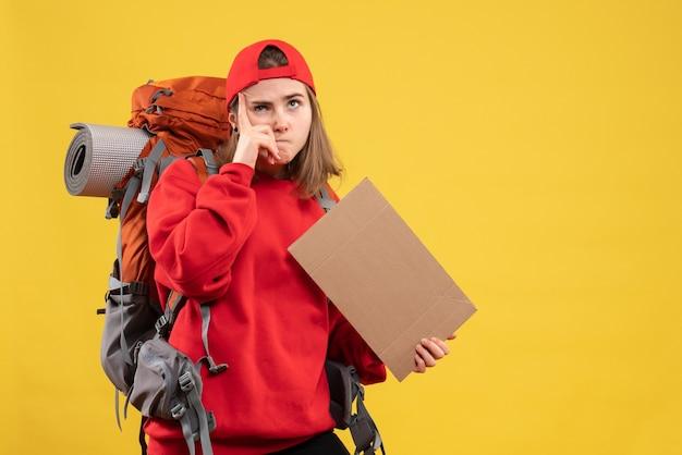 Vue de face de l'auto-stoppeur féminin intéressé tenant un carton vierge