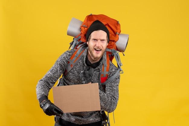 Vue de face de l'auto-stoppeur mâle barbu avec des gants en cuir et sac à dos tenant du carton vierge